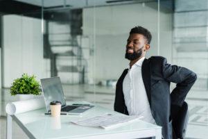 o que acontece com quem trabalha muito tempo sentado - imagem de jovem trabalhando sentado no escritório com dor nas costas região lombar